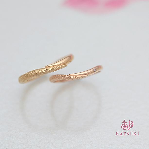 半周ずつ2つのデザインを施した結婚指輪